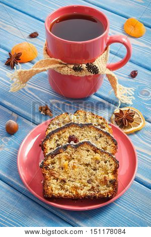 Cup of hot tea and pieces of fresh baked homemade fruitcake on plate on boards delicious festive dessert