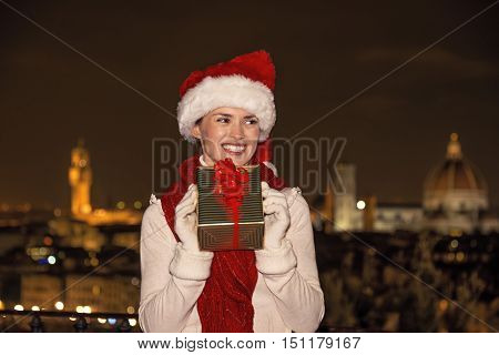 Happy Woman In Florence, Italy With Christmas Gift Looking Aside