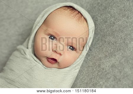 A newborn baby is 9 days old wrapped in a grey cloth like a Russian doll. Beautiful boy was awake and quietly watching