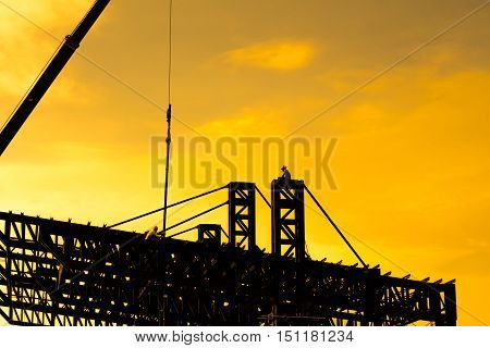 Steel structure of the roof. Workers are building the roof in the evening.