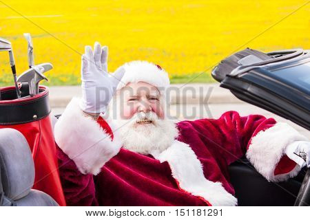 Santa waves on his way to the golf course from his convertible with the top down