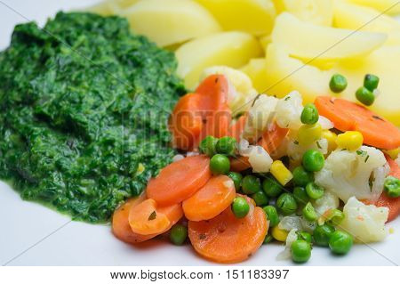 Fresh spinach with potatoes carrots and peas. Delicious vegetables. Healthy and tasty vegetables.