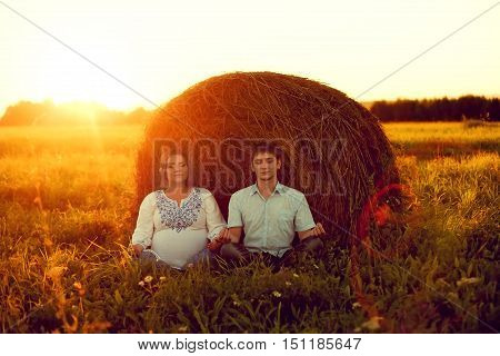 Happy couple husband and wife meditate on the nature near the haystack. Meditation at sunset in the summer while pregnant