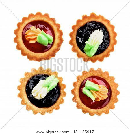 Arrangement of Delicious Little Tarts with Colored Butter Cream Fruit Jam and Decoration closeup on White background. Top View