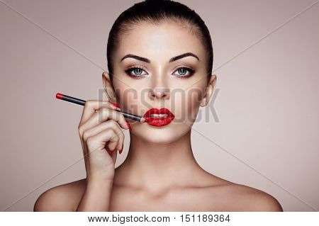 Beautiful woman paints lips with lipstick. Beautiful woman face. Makeup detail. Beauty girl with perfect skin