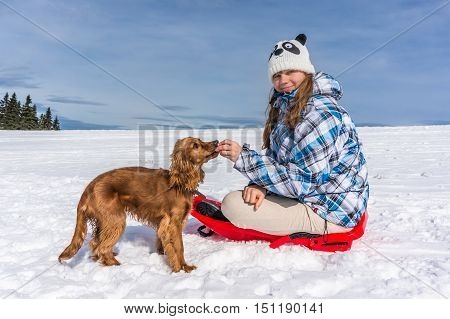 Beautiful woman with her dog on the snow in winter