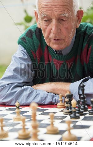Mature man playing chess in the garden