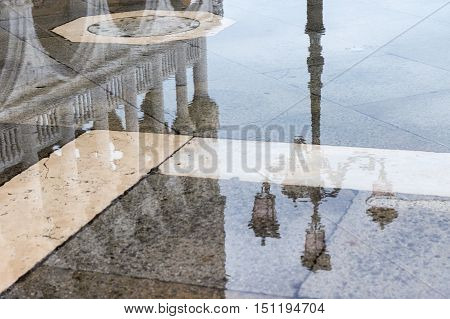 Reflection of Doge's Palace in a pool on St Mark's Square (Venice Italy)