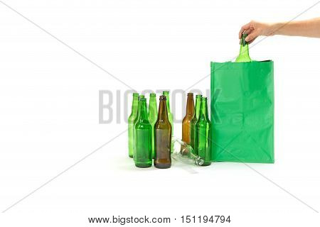 Used glass bottles are standing on the white background. Woman's hand is inserting glass bottle into an empty green bag. All potential trademarks are removed.