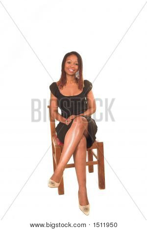 Professional Young Black South African Lady Business Woman In Black Dress Sitting On Chair