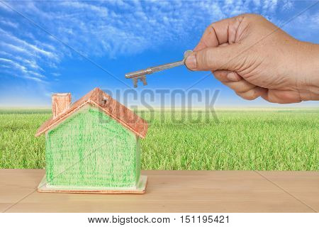 house key with a miniature model house on landscape background