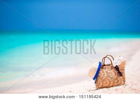 Beach accessories - bag, straw hat, sunglasses on white beach