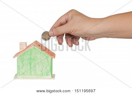 hand push a coin in to money box concept for mortgage or real state investment