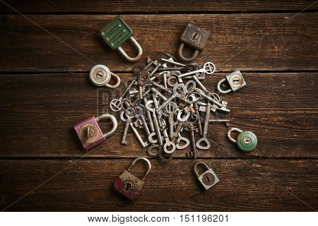 Group of old rusty padlocks with pile of keys on brown wooden table