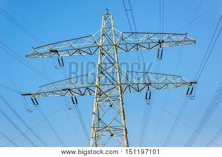 One iron power pylon and many high voltage lines against a clear blue sky on a sunny day in the summer season.