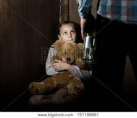 Sad little girl sitting against the wall in despair. In his hands he holds an teddy bear. drunken man threatens