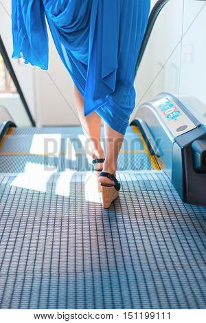 young woman's legs stepping on an escalator