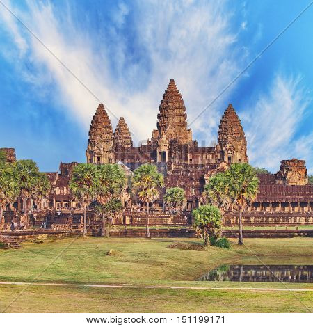 Angkor Wat temple with grass lawn and stones on foreground