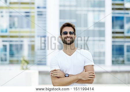 Confident guy in white t-shirt portrait in town