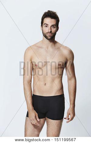 Shirtless guy in black shorts portrait - in studio