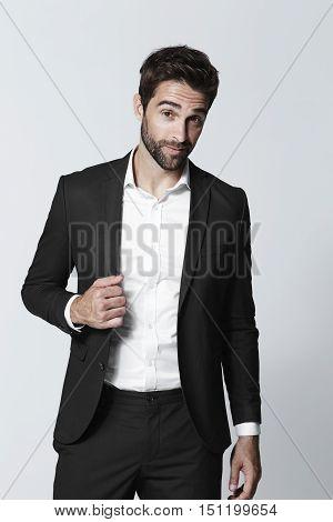 Black suited dude in studio portrait -grey background