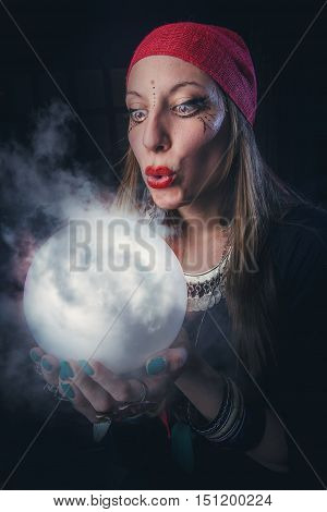 Witch halloween: gypsy sorceress casting spells using her crystal ball, using her knowledge of magic to manipulate reality