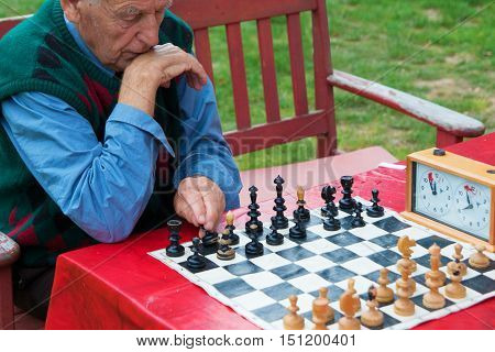 Old man thinking and playing chess in the garden
