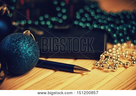 Christmas balls and ballpoint pen on a wooden table
