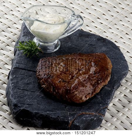 Delicious Roast Beef with Rosemary and Blue Cheese Sauce on Stone Plate closeup on Wicker background