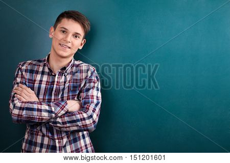 Young Man Standing with Arms Folded Against Blackboard