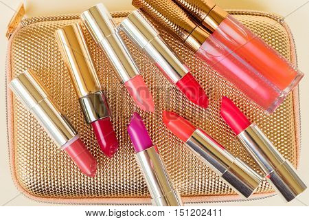Collection of red and pink lipsticks on golden woman pursue background