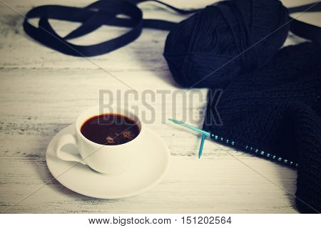 Black knitting, ribbon and coffee,  All Souls Day, focused on needles,  filtered picture