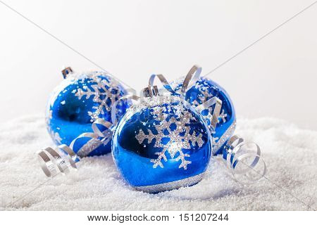 Blue Christmas Baubles with the Fake Snow on the Grey Background