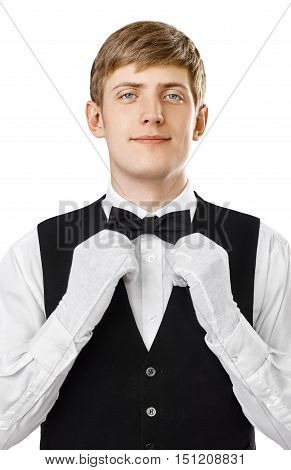 Portrait of young handsome waiter fixing his bow tie on a suit isolated on white background
