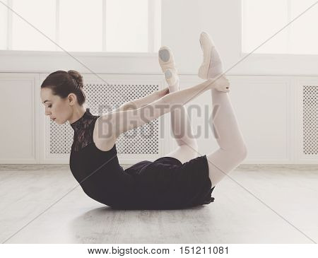 Classical Ballet dancer side view. Beautiful graceful ballerine in black practice bow pose, making yoga stretching in light hall. Ballet class training, high-key soft toning, copy space