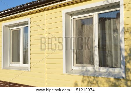 wall of the house with two windows coated with yellow siding