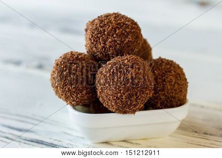 Brown sweets in a bowl. Small desserts covered in crumbs. Freshly cooked chocolate rum balls. Sweet dish with alcohol.