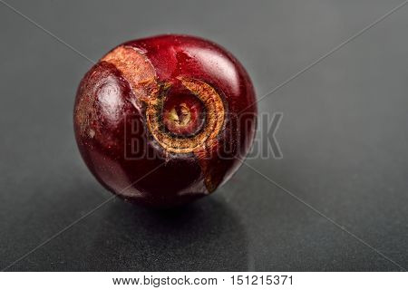 Close Up Of Image Of Rotten Red Cherry Fruit On Reflective Black Background. Selective Focus.