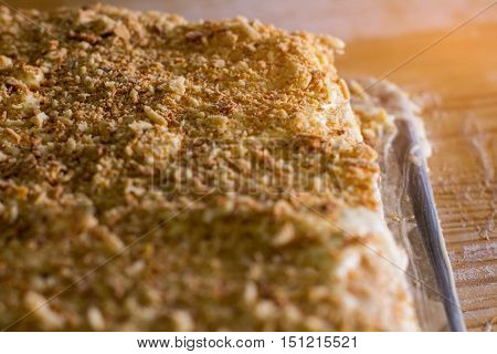 Dessert with cookie crumbs. Cake under sunlight. Puff dough and cream. Freshly made sweet dish.