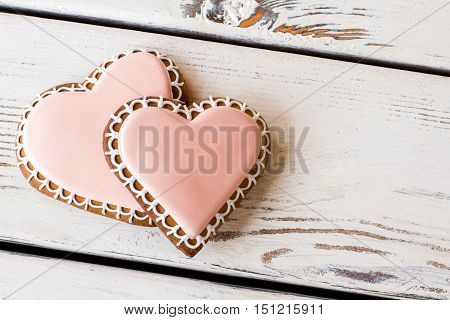 Pair of heart-shaped cookies. Biscuits on white wooden surface. Easy recipe of happiness. Treats for loving couple.