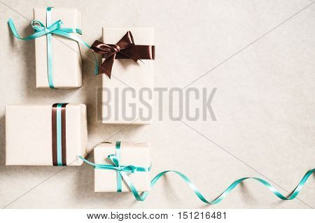 Holiday background with four gift boxes wrapped in kraft paper and ribbon