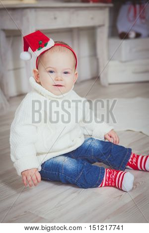 Smiling funny girl in Santa red hat Sitiing and smile. Christmas concept. Christmas decoration