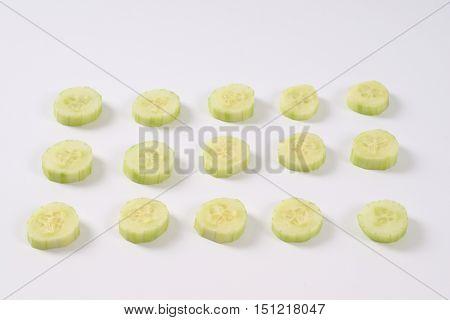 slices of fresh cucumber arranged on white background