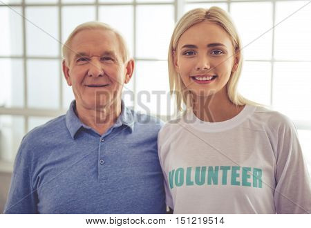 Beautiful young female volunteer and handsome old man are looking at camera and smiling