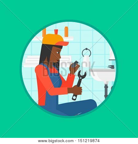 An african-american plumber sitting in a bathroom and repairing sink pipe. Woman with wrench repairing a broken sink in bathroom. Vector flat design illustration in the circle isolated on background.
