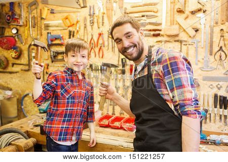 family, carpentry, woodwork and people concept - father and little son with hammers at workshop