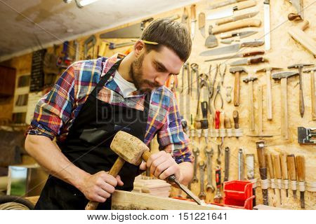 profession, carpentry, woodwork and people concept - carpenter with hammer and chisel processing wood plank at workshop