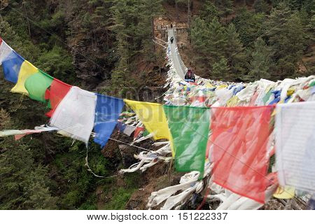 Rope hunging suspension bridge with row of prayer flags under Namche Bazar village way to Everest base camp Nepal