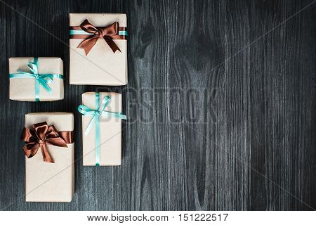 Holiday background with four gift boxes wrapped in kraft paper