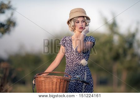 Vintage 1930S Fashion Woman In Blue Summer Dress Standing With Bicycle In Rural Landscape.